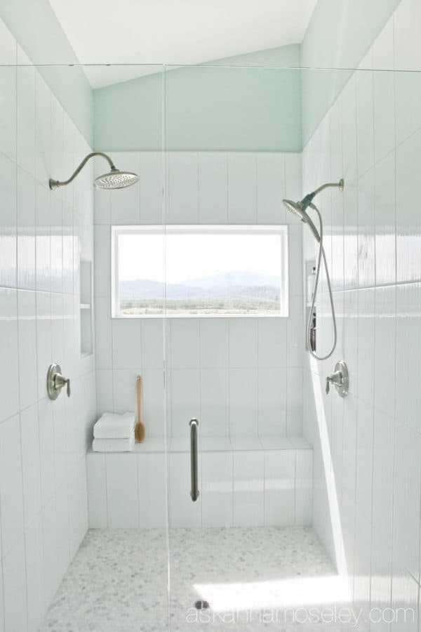 Master bathroom shower with dual shower heads and a panoramic window | Ask Anna