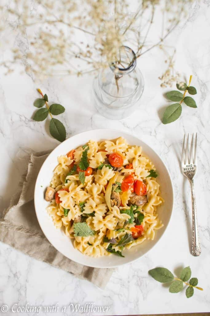 Bow tie pasta tossed with roasted mushrooms, tomatoes, onions, fresh herbs, and a drizzle of olive oil. This roasted mushroom tomato pasta is delicious, and a great choice for a quick and easy weeknight dinner   Cooking with a Wallflower