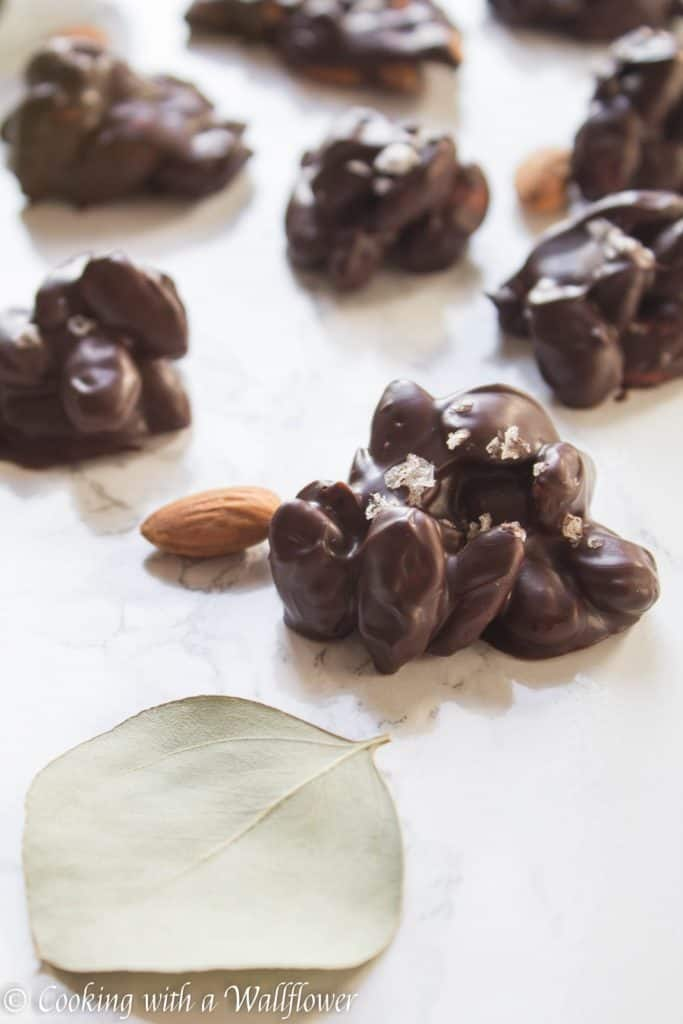 Roasted almonds coated with semi sweet chocolate then topped with a pinch of vanilla salt. These chocolate covered almond clusters are so simple to make and perfect for gifting. | Cooking With a Wallflower