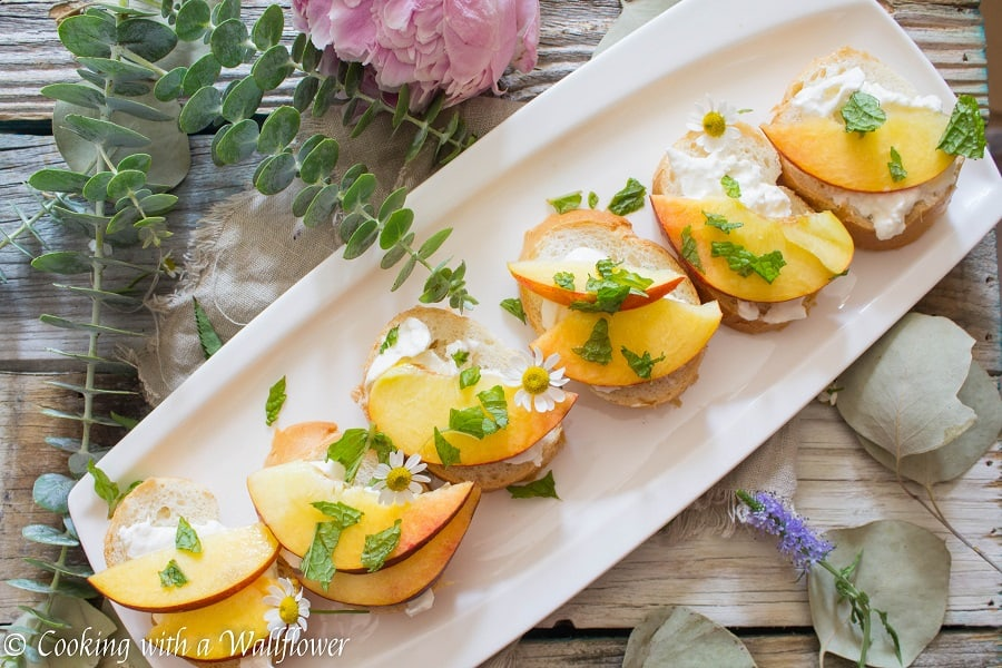 Crispy bread topped with fresh peaches, creamy burrata, mint and a sweet, tangy, honey, lemon dressing. Super fresh, easy to make, and pleasantly delicious, this peach burrata toast is the perfect appetizer for summer guests.   Cooking with a Wildflower