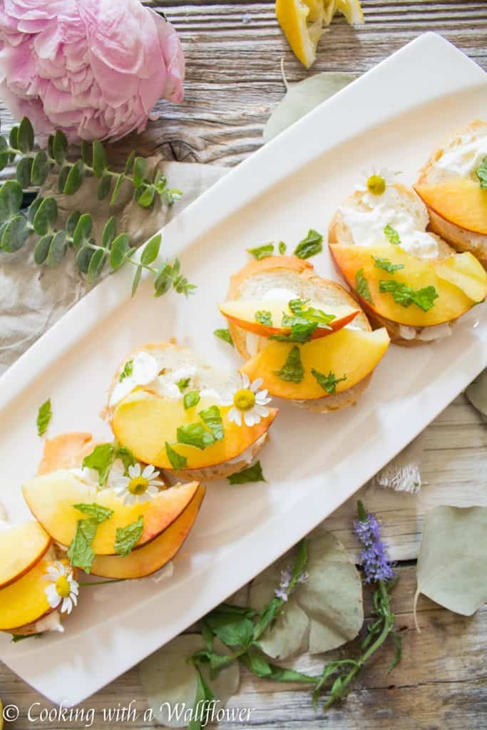 Crispy bread topped with fresh peaches, creamy burrata, mint and a sweet, tangy, honey, lemon dressing. Super fresh, easy to make, and pleasantly delicious, this peach burrata toast is the perfect appetizer for summer guests. | Cooking with a Wildflower