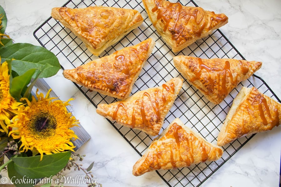 Puff pastries filled with cinnamon apples and drizzled with salted caramel, these salted caramel apple turnovers are simple to make and delicious. | Cooking with a Wallflower