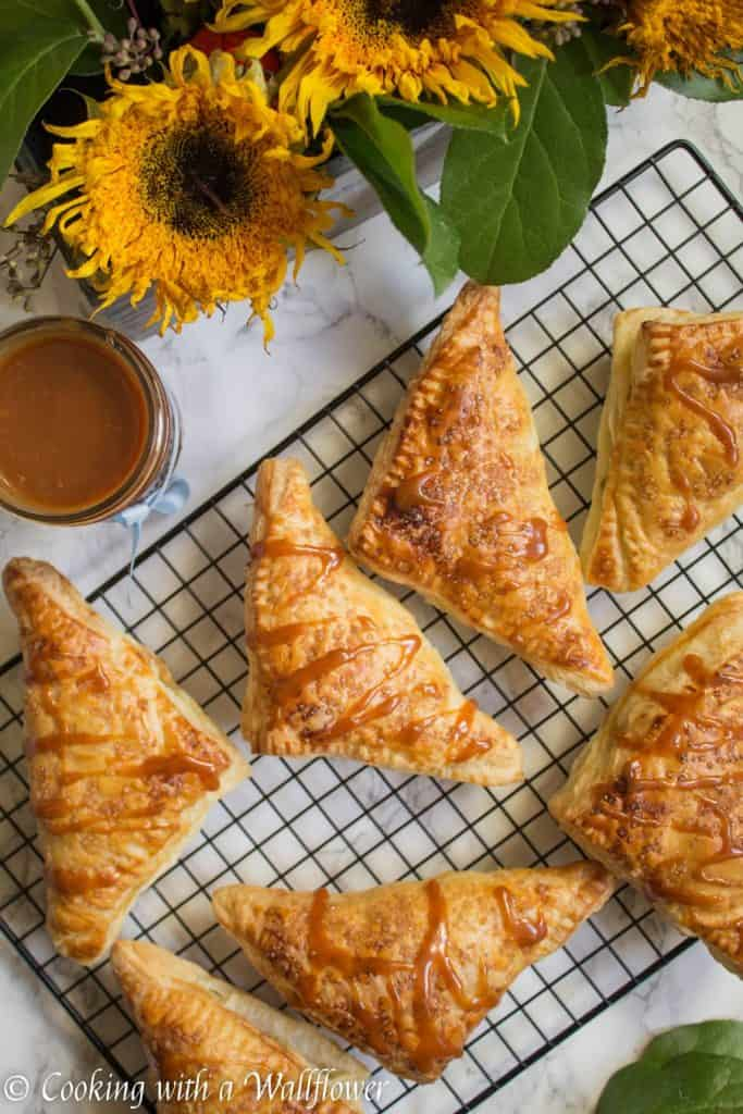 Puff pastries filled with cinnamon apples and drizzled with salted caramel, these salted caramel apple turnovers are simple to make and delicious.   Cooking with a Wallflower