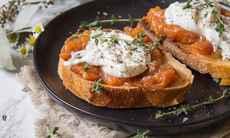 Toast topped with sweet peach jam, creamy burrata, thyme, salt and pepper. This Peach Jam Burrata Toast is delicious and perfect for breakfast or a late summer snack. | Cooking with a Wallflower