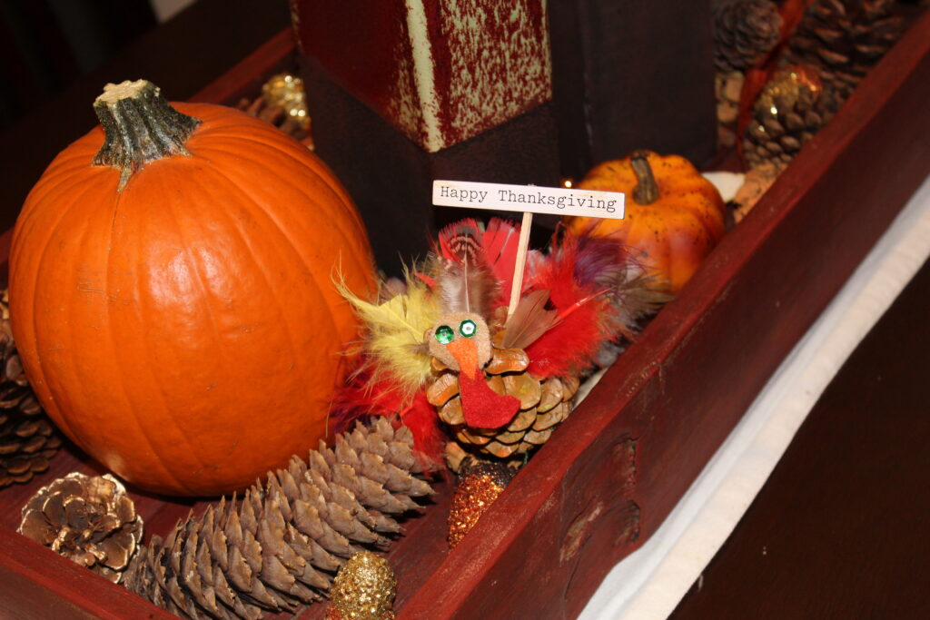 A table with Thanksgiving decorations and a pinecone turkey craft. Words that say Happy Thanksgiving!