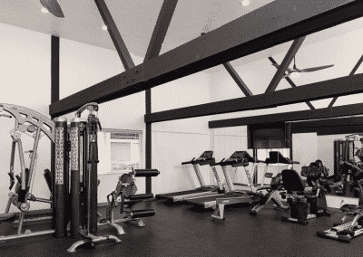fitness center with exposed beams and workout equipment