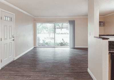 empty living room with view of kitchen and front door