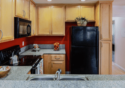 kitchen with quartz counters, maple cabinets, and black appliances