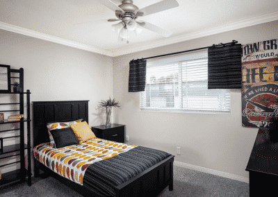 Furnished bedroom with ceiling fan and window