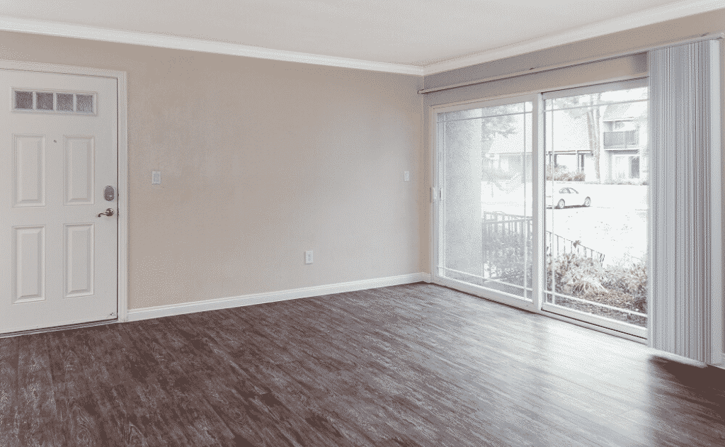 Empty living room with ceiling fan and window