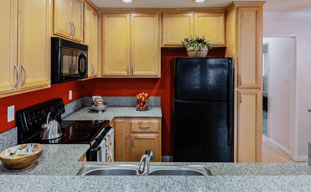 Kitchen with black appliances and countertops with decor