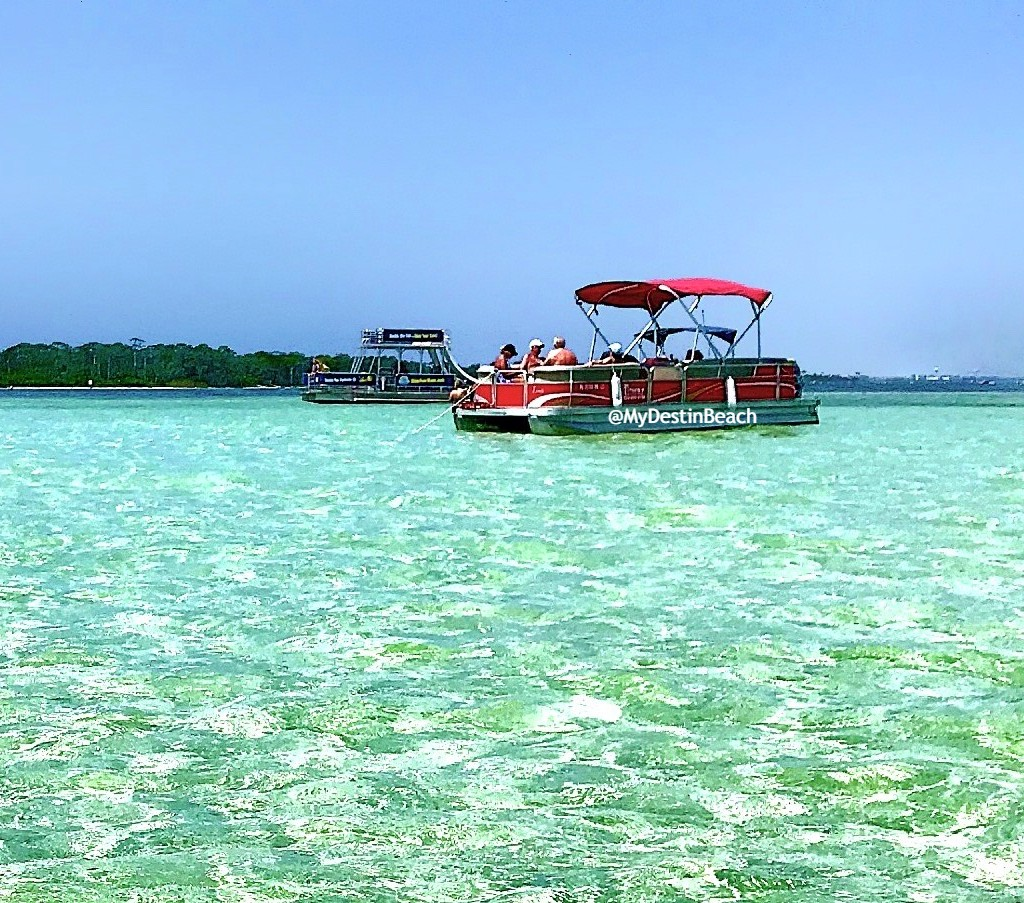 Red pontoon boat in the middle of the waters of Crab Island, Destin, Florida.