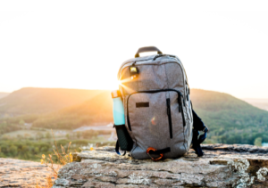 Do we need a survival kit? Full backpack with water bottle sitting on log at sunrise