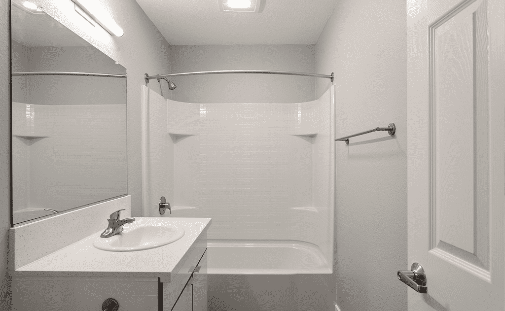 White bathroom with mirror, bathtub and shower, and sink