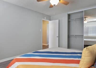 Bedroom with bed facing the open door and showing open closet
