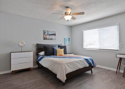 The Circle Apartments Guest Bedroom with ceiling fan, window with blinds, and frames on the wall