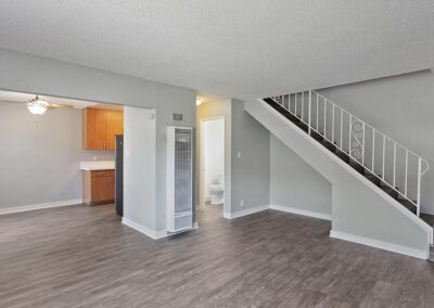 Empty living room with view of stairs and kitchen