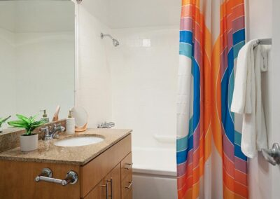 Master Bathroom with wide mirror in front of colorful curtain, wood cabinet over marbled sink
