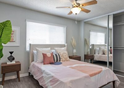 Furnished Master Bedroom with Ceiling Fan and Mirror Closet