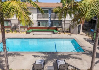 The Circle Apartments Pool with outdoor seating and palm trees