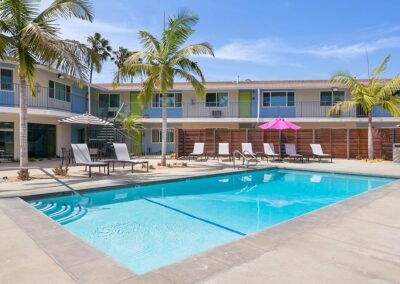 The Circle Apartments Pool with Palm Trees and lounge Chairs