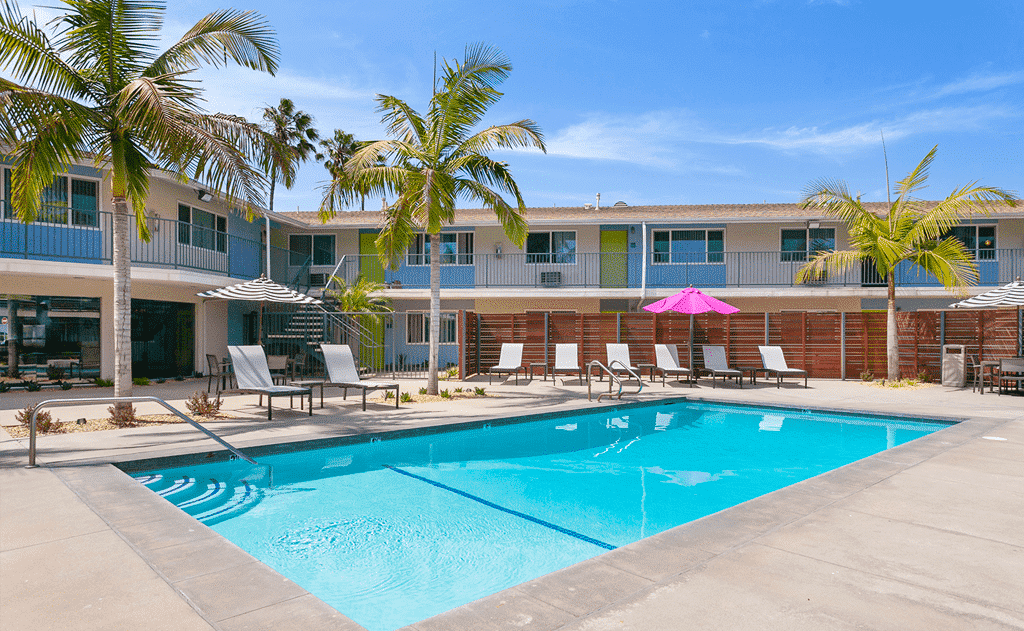 The Circle Apartments Swimming Pool with lounge chairs and palm trees