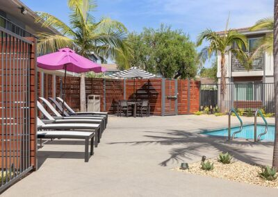 The Circle Apartments Poolside recliners with pink umbrella