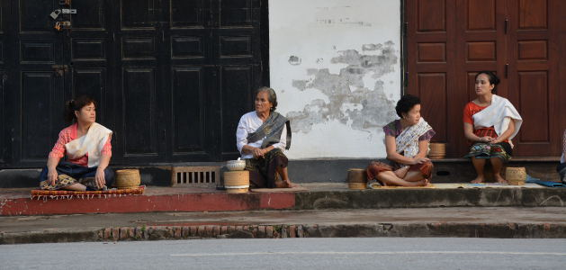 Locals wait patiently with to give monks their alms of steamed sticky rice.
