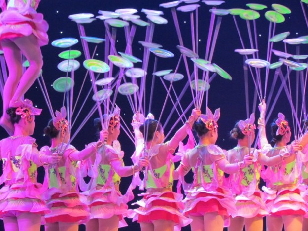 From Lina: This shot was taken at an Acrobatic show in Beijing, China. There were many acts with just a few people on the stage, but the plate spinners started off small and got more chaotic as their act went on.