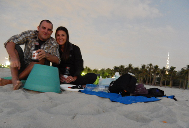 Picnic on the beach with wine in juice bottles.