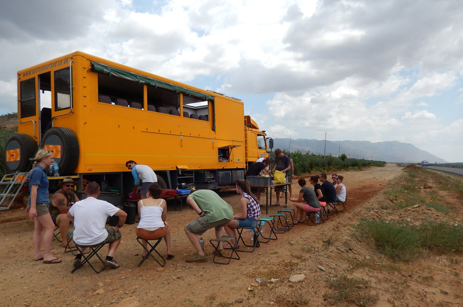 Dan and his cooking team chopping avocados on the side of the road while the group patiently waits.
