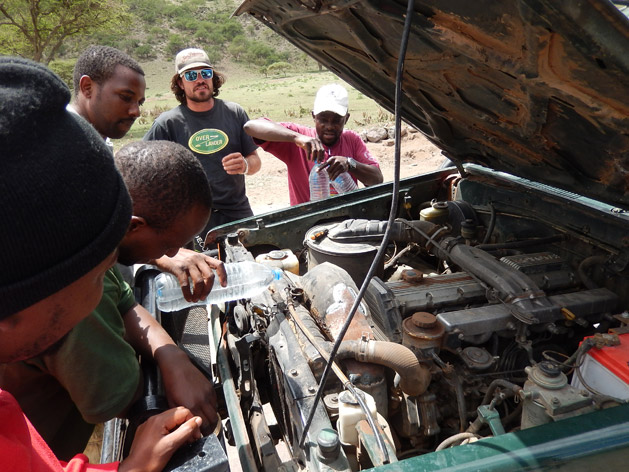 Our guide Joe speaks with our safari drivers as they try to fix our radiator.  Knowing very little about cars is another reason I'm glad we booked an overland tour instead of trying to drive ourselves.