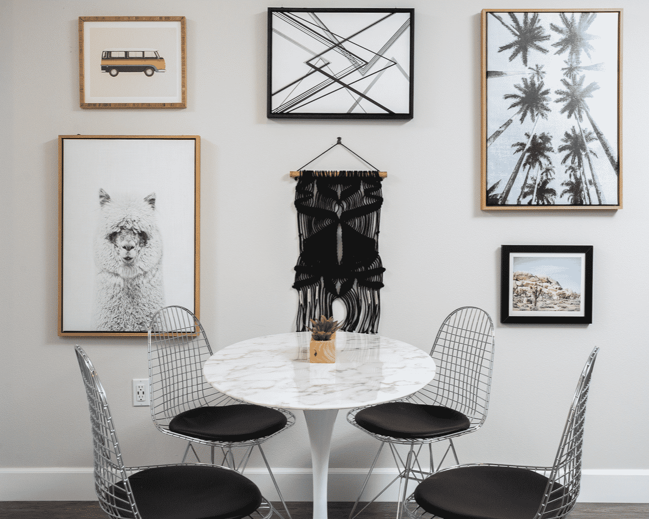 Marble round table with a four metal chairs and paintings on the wall