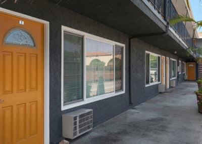 Exterior of apartments with orange door and huge glass windows