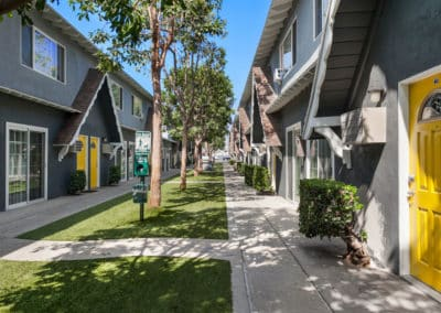 Pathway surrounded by grass and trees next to apartment homes
