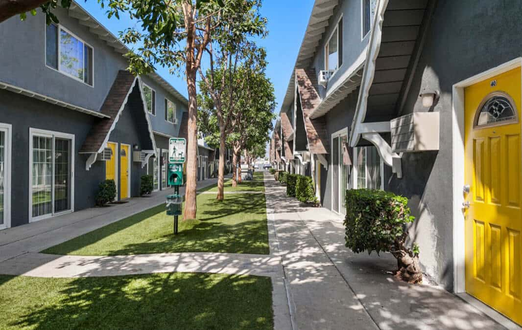 Walkway through Northwind Apartment Homes with yellow doors and trees