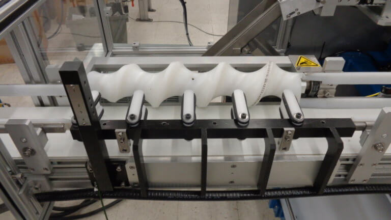 A timing screw controls incoming product off a continuous conveyor.