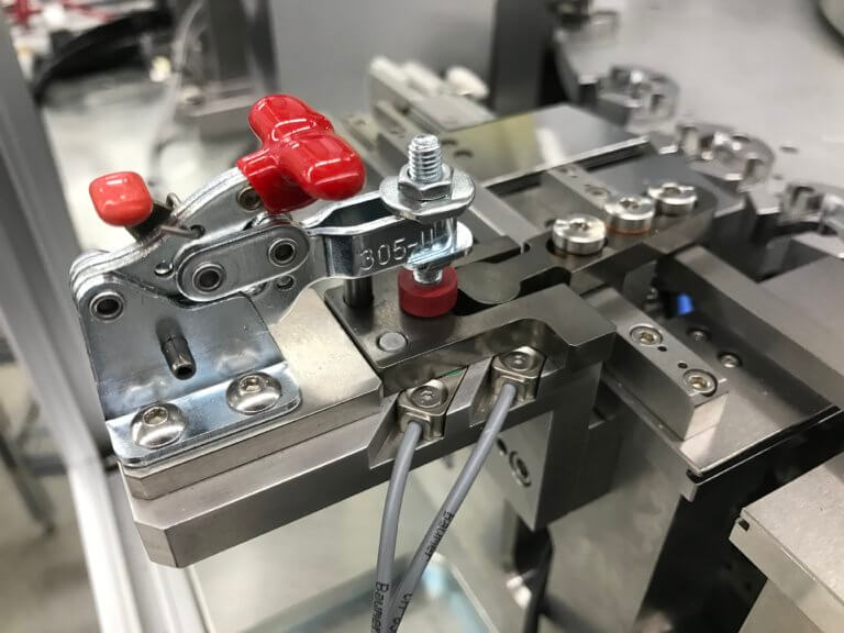 A commercial toggle clamp is used to help retain a custom piece of changeover tooling.