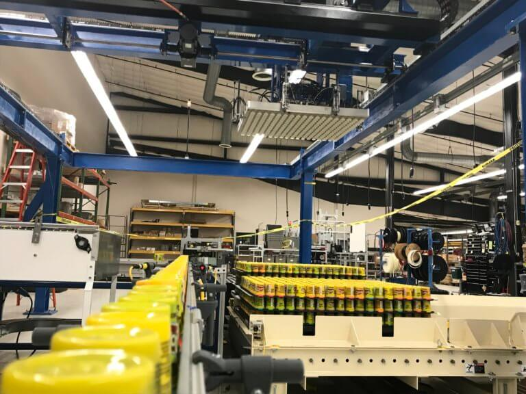 Product is conveyed to a collation table for an overhead gantry to palletize.