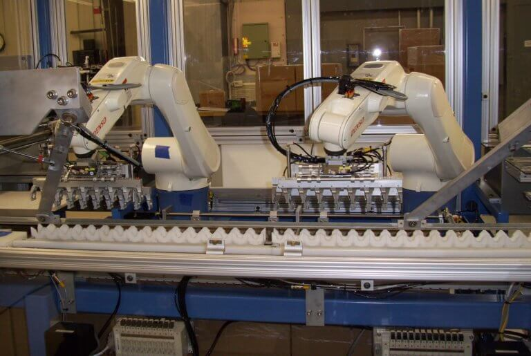 Twin DENSO six-axis robots load customer product into boxes for packing.