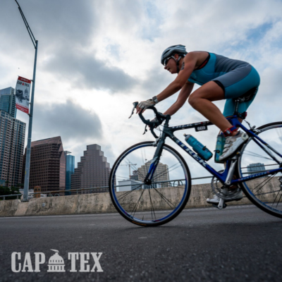 Cyclist crosses South 1st Street bridge with the Austin skyline as the backdrop during the CapTex Tri.