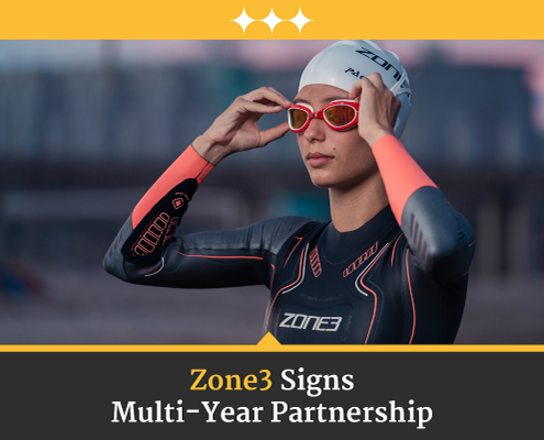 Female triathlete adjusts her goggles before she swims in her Zone3 wetsuit. Text on design reads Zone3 Signs Multi-Year Partnership. Learn more at https://captextri.com/zone3-usa-partnership/