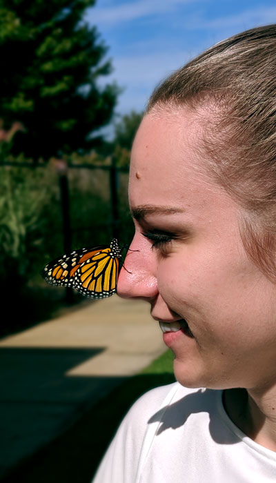 woman with a Monarch Butterly landed on her nose