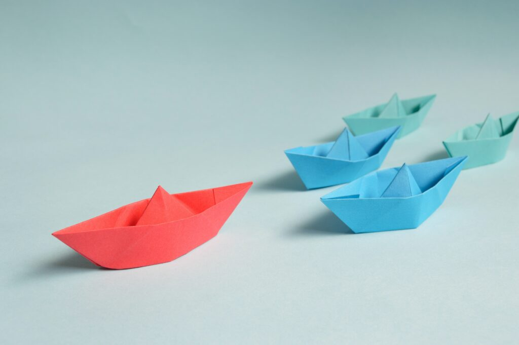 A group of paper boats with a red paper boat leading the others
