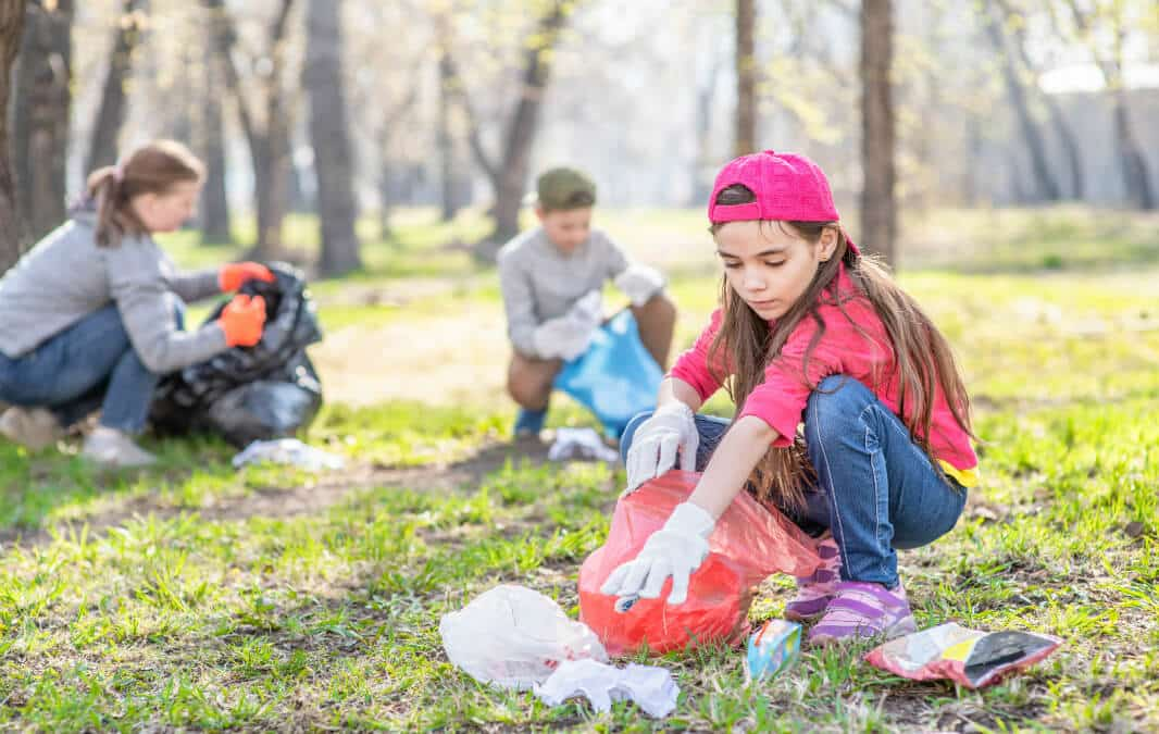 a child picking up trash in the park with a woman and another child in the background