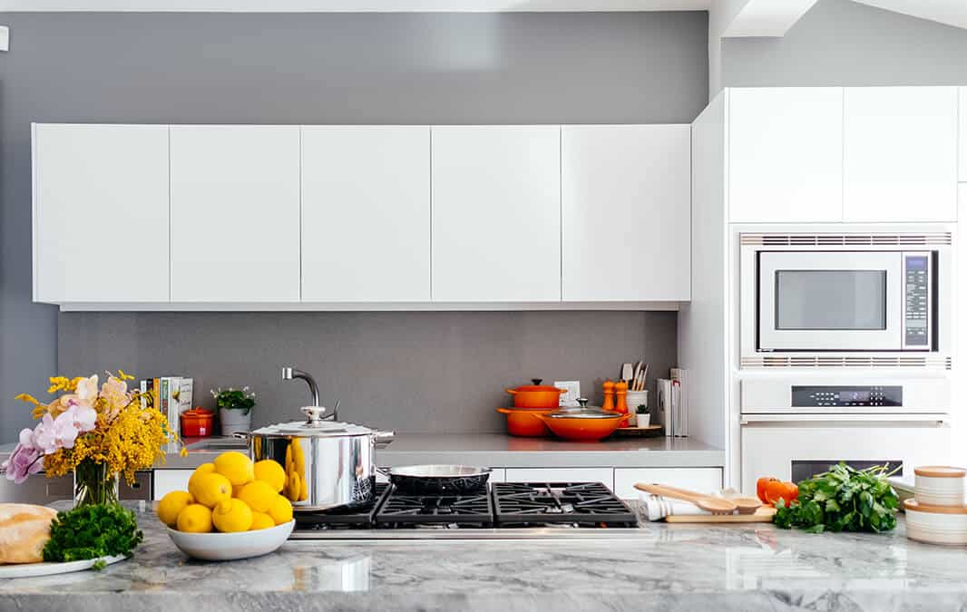 sleek kitchen with fruits and vegetable on top of the counter