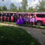 Quinceañera in purple dress atanding near Johnny B's Pink Limo in Charlotte NC