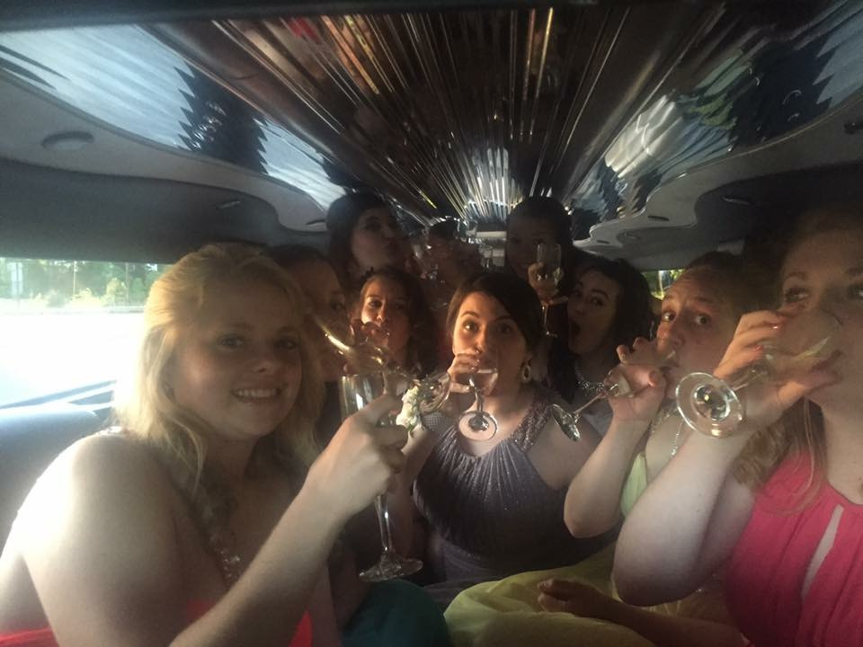 Charlotte Prom Limo drinking grape sparkling juice out of champagne flutes for fun in the silver hummer limo