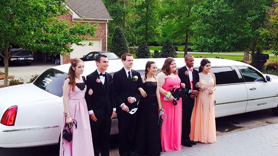 Carolina Luxury Transportation Group's white Lincoln Prom Limo picking up prom students in Charlotte NC for a party
