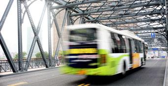 city bus on the road crossing a bridge